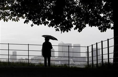 A man holds an umbrella as he looks out at London's Canary Wharf financial district from Greenwich park, July 2, 2012. REUTERS/Andrew Winning