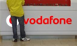 Покупатель стоит перед витриной с логотипом Vodafone в магазине в Праге, 7 февраля 2012 года. Vodafone списал 5,9 миллиарда фунтов стерлингов ($9,4 миллиарда) со стоимости своих активов в Испании и Италии, а также снизил целевой прогноз на весь год после первого с 2010 года спада органической выручки от реализации услуг во втором квартале. REUTERS/David W Cerny