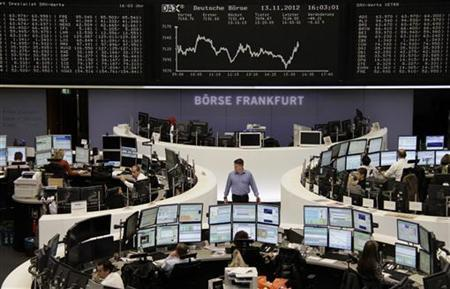 Traders are pictured at their desks in front of the DAX board at the Frankfurt stock exchange November 13, 2012. REUTERS/Remote/Staff (GERMANY - Tags: BUSINESS)