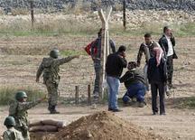 Francia se convirtió el martes en la primera potencia europea en reconocer a la nueva coalición opositora de Siria como el único representante del pueblo y dijo que estudiaría la petición de armas que realizaron sus líderes una vez que establezca un Gobierno de transición. En la imagen, soldados turcos hablan con refugiados sirios que intentan cruzar la valla fronteriza entre el pueblo de Ras al Ain, en el norte de Siria, y Turquía durante un ataque aéreo en territorio sirio, visto desde la localidad fronteriza de Ceylanpinar, en la provincia turca de Sanliurfa, el 13 de noviembre de 2012. REUTERS/Osman Orsal