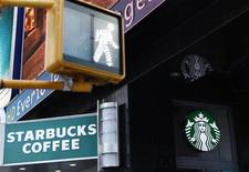 A walk sign flashes in Times Square in front of a store bearing the new Starbucks logo in New York March 8, 2011. REUTERS/Lucas Jackson