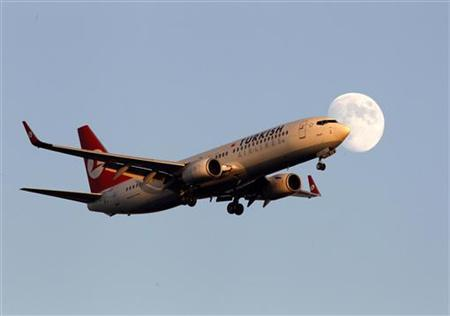 A Turkish Airlines Boeing 737-800 plane flies past the moon as it lands at Ataturk International Airport in Istanbul October 26, 2012. REUTERS/Osman Orsal (TURKEY - Tags: TRANSPORT)