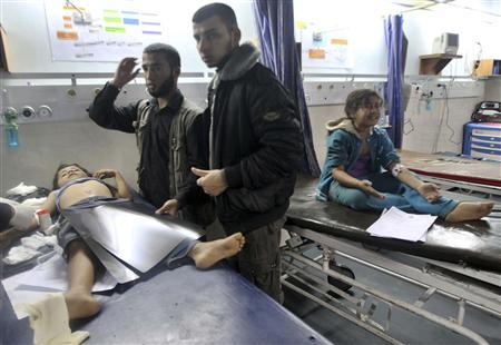 Palestinians stand next to wounded children at a hospital after an Israeli air strike in Gaza City November 14, 2012. REUTERS/Mohammed Salem