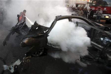 A Palestinian helps extinguish the fire after an Israeli air strike on a car in Gaza City November 14, 2012. REUTERS/Ali Hassan