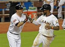 Miami Marlins shortstop Jose Reyes (R) celebrates with teammate Gil Velazquez after Reyes scored the winning run over the New York Mets on a bases loaded 11th inning single by teammate Donovan Solano during their MLB National League baseball game in Miami, Florida, October 2, 2012. REUTERS/Joe Skipper