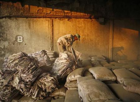 A labourer works inside a cement storage godown at an industrial area in Mumbai November 6, 2012. REUTERS/Danish Siddiqui