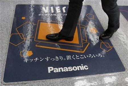 A man walks on a Panasonic Corp's Viera TV advertisement at an electronics store in Tokyo November 15, 2012. REUTERS/Toru Hanai