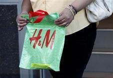 Женщина держит в руках пакет H&M в магазине компании в Голливуде 26 января 2011 года. Сравнимые продажи Hennes & Mauritz, второго по величине в мире ритейлера одежды, неожиданно упали на 5 процентов в октябре 2012 года из-за слабости спроса в затронутой кризисом Европе. REUTERS/Fred Prouser