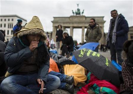 Afghan refugee Ali Reza sits in front of Brandenburg Gate during a hunger strike in Berlin October 25, 2012. REUTERS/Thomas Peter (GERMANY - Tags: POLITICS CIVIL UNREST)