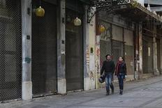 A couple walks past closed shops in Athens January 13, 2012. REUTERS/Yiorgos Karahalis