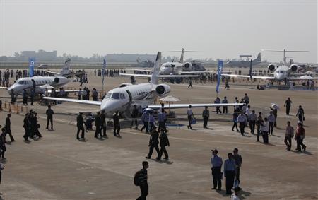 Visitors walk around business jets on display on the first day of the China International Aviation & Aerospace Exhibition in the southern Chinese city of Zhuhai November 13, 2012. REUTERS/Bobby Yip
