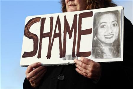Mary Phelan holds a picture of Savita Halappanavar in protest outside University Hospital Galway in Galway, Ireland November 15, 2012. REUTERS/Cathal McNaughton