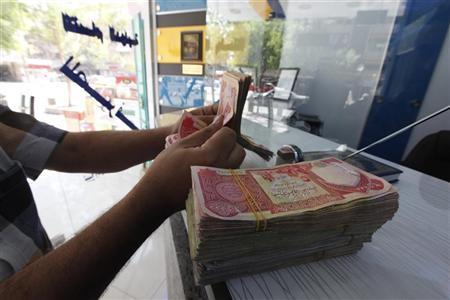 A customer counts Iraqi dinars at a money changer in Baghdad October 1, 2012. REUTERS/Saad Shalash