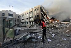 Палестинский пожарный пытается потушить огонь после авиаудара израильских ВВС по зданию МВД ХАМАС в Газе, 16 ноября 2012 года. Визит премьер-министра Египта Хишама Кандиля в сектор Газа не смог даже на время потушить конфликт между Палестинской автономией и Израилем, вспыхнувший два дня назад. REUTERS/Mohammed Salem
