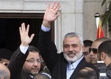 Premiê egípcio, Hisham Kandil (E) e líder sênior do Hamas Ismail Haniyeh acenam para o povo na Cidade de Gaza. 16/11/2012 REUTERS/Ahmed Zakot