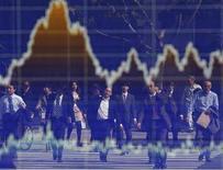"""Люди отражаются в экране с колебаниями котировок у Токийоской фондовой биржи 7 ноября 2012 года. Глобальные инвесторы по-прежнему не интересуются европейским регионом в связи с долговыми проблемами стран, и на этом фоне ориентированные на РФ фонды ощущают отток средств шестую неделю подряд, тогда как азиатские рынки получили репутацию """"тихой гавани"""". REUTERS/Toru Hanai"""