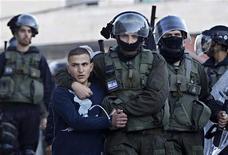 Soldado de segurança israelense segura palestino que atirava pedras durante protesto contra a operação militar de Israel em Gaza, em Jerusalém oriental. Sirenes de ataque aéreo soaram em Jerusalém nesta sexta-feira e a Rádio do Exército de Israel disse que o alerta era para as cidades israelenses perto da cidade sagrada. 15/11/2012 REUTERS/Ammar Awad