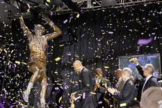 """(L - R)Former Los Angeles Lakers basketball player and NBA Hall of Famer Kareem Abdul-Jabbar looks at a bronze statue of himself as it is unveiled, while others including Earvin """"Magic"""" Johnson, James Worthy, Richard Lapchick, Eddie Doucette and Pat Riley stand with him, in Star Plaza, outside Staples Center in Los Angeles November 16, 2012. REUTERS/Danny Moloshok"""