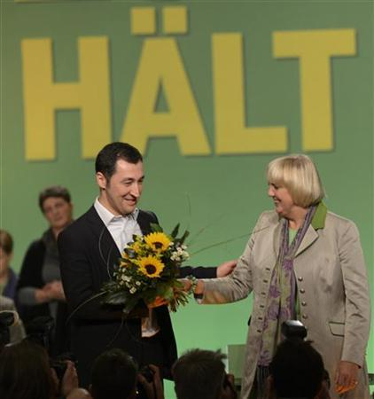 German Green Party leaders Claudia Roth (R) and Cem Oezdemir are surrounded by media after their re-election at the party convention of the Green Party in Hanover, November 17, 2012. Slogan is reading: ''Stay''. REUTERS/Fabian Bimmer