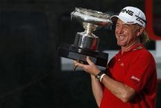Miguel Angel Jimenez of Spain poses with his trophy and a cigar after winning the Hong Kong Open golf tournament November 18, 2012. REUTERS/Tyrone Siu