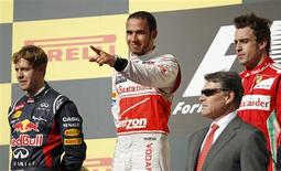 McLaren Formula One driver Lewis Hamilton of Britain gestures next to Red Bull Formula One driver Sebastian Vettel (L) of Germany, Ferrari Formula One driver Fernando Alonso (R) of Spain and Texas Governor Rick Perry (in suit) during the podium ceremony after the U.S. F1 Grand Prix at the Circuit of the Americas in Austin, Texas November 18, 2012. Hamilton won the U.S. Grand Prix on Sunday while championship leader Vettel failed to clinch his third consecutive drivers' title on his 100th career start. Alonso came in third. REUTERS/Robert Galbraith