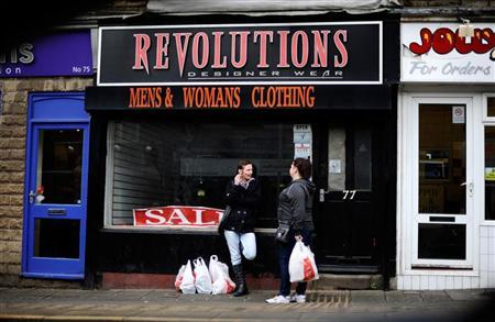 Women chat outside a vacant, closed down store as a man looks out from a fish and chip shop in the heart of Sheffield, northern England January 25, 2012. REUTERS/Dylan Martinez