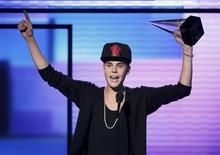 "Justin Bieber accepts the award for favorite pop rock album for ""Believe"" at the 40th American Music Awards in Los Angeles, California, November 18, 2012. REUTERS/Danny Moloshok"