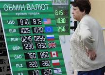 Женщина стоит у обменного пункта на центральной улице Киева 30 августа 2012 года.Украина, стремясь найти инструменты защиты гривны от девальвации и пополнения опустевшей в год выборов казны, думает ввести 15-процентный сбор при обмене наличной валюты на национальную, что может ограничить население в способах сбережения заработанного и стимулировать черный рынок. REUTERS/Anatolii Stepanov