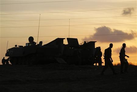 Israeli soldiers walk past an armoured personnel carrier (APC) outside the northern Gaza Strip November 19, 2012. REUTERS/Amir Cohen