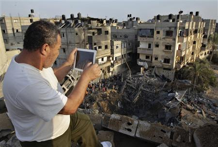 A Palestinian man uses his iPad as he takes pictures of a destroyed house after an Israeli air strike in Khan Younis in the southern Gaza Strip November 19, 2012. REUTERS/Ibraheem Abu Mustafa