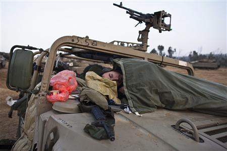 Israeli soldiers sleep on a military vehicle at a staging area near the border with the Gaza Strip November 19, 2012. REUTERS/Nir Elias