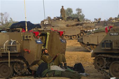 An Israeli soldier reads as he leans on an armoured personnel carrier (APC) at a staging area near the border with the Gaza Strip November 19, 2012. REUTERS/Ronen Zvulun