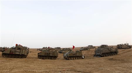 Israeli armoured personnel carriers (APC) and tanks are seen at a staging area near the border with the Gaza Strip November 19, 2012. Israel bombed dozens of suspected guerrilla sites in the Hamas-ruled Gaza Strip on Monday and Palestinian rocket fire from the enclave dropped off as international efforts to broker a truce intensified. REUTERS/Ronen Zvulun