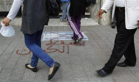 People step on a drawing of an Israeli flag, drawn by Tunisians in support of Palestinian people during Israel's ongoing military operation in Gaza, in front of a mall in Tunis November 19, 2012. The writing reads, ''Zionism entity''. REUTERS/Zoubeir Souissi