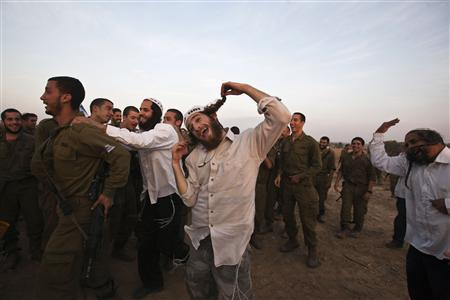 Hasidic Jewish men, from the Breslov sect, dance with Israeli troops during a visit to support the soldiers, near the border with the Gaza Strip November 19, 2012. REUTERS/Nir Elias