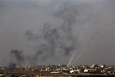 Black smoke rises after an Israeli air strike and smoke trails are seen as three rockets are launched from the central Gaza Strip towards Israel November 19, 2012. REUTERS/Yannis Behrakis