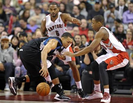 Minnesota Timberwolves guard Brandon Roy (L) grabs a loose ball in front of Toronto Raptors defenders Alan Anderson and DeMar DeRozan (R) during the first half of their NBA basketball game in Toronto November 4, 2012. REUTERS/Mike Cassese