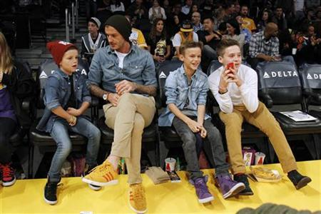 British soccer player David Beckham (2nd L) sits courtside with his sons Cruz (L), Romeo (2nd R) and Brooklyn (R) before the NBA basketball game between the Los Angeles Lakers and Phoenix Suns in Los Angeles November 16, 2012. REUTERS/Danny Moloshok