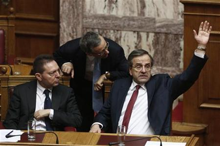 Greek Prime Minister Antonis Samaras (R) votes during a voting for the 2013 budget as Finance Minister Yannis Stournaras (L) looks on at the parliament in Athens early November 12, 2012. Greece's ruling coalition secured enough votes in parliament on Sunday to approve the 2013 budget law, a crucial requirement for Athens to revive its stalled international bailout programme and avoid insolvency. REUTERS/Yorgos Karahalis (GREECE - Tags: POLITICS BUSINESS)