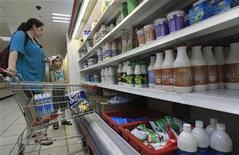Женщина с ребенком выбирают продукты в супермаркете в Москве, 1 августа 2012 года. Крупнейший по выручке российский продуктовый ритейлер X5 Retail Group получил $12,1 миллиона чистой прибыли по МСФО в третьем квартале 2012 года после убытка в $2,1 миллиона годом ранее, сообщила компания во вторник. REUTERS/Sergei Karpukhin
