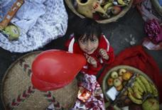 La educación, la alimentación y el medio ambiente son las principales preocupaciones de los niños de todo el mundo, y particularmente para los que crecen en los países en vías de desarrollo, según un sondeo internacional difundido el martes. En la imagen, un niño sentado mientras su madre hace una ofrenda junto al río Bagmati, en Katmandú, el 18 de noviembre de 2012. REUTERS/ Navesh Chitrakar