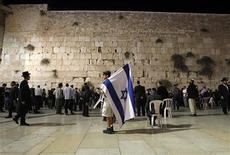 """Un misil lanzado contra Jerusalén el martes no alcanzó la ciudad ni causó víctimas, dijo la policía israelí. """"No hay indicios de la caída de un cohete en la ciudad"""", dijo un portavoz de la policía al Canal 2 de Israel. En la imagen, un hombre sujeta una bandera israelí durante una oración en el Muro de las Lamentaciones el 18 de noviembre de 2012. REUTERS/Baz Ratner"""