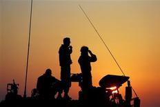 Israel y milicianos de la Franja de Gaza acordaron el martes un alto el fuego mediado por Egipto que entrará en efecto a la medianoche local, según el miembro de Hamás Ayman Taha, en declaraciones a Reuters desde El Cairo. En la imagen, soldados israelíes sobre una unidad de artillería móvil posicionada a las afueras de Gaza, el 20 de noviembre de 2012. REUTERS/Darren Whiteside