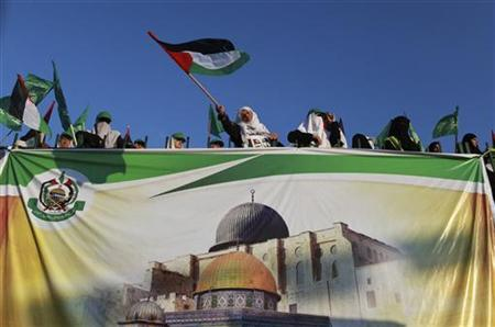 Hamas supporters wave flags as they stand behind a banner depicting the Dome of the Rock and Al-Aqsa Mosque during a rally in Gaza City August 30, 2012. REUTERS/Mohammed Salem/Files