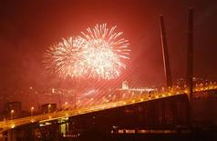 Фейерверк 8 сентября 2012 года над мостом во Владивостоке, построенном к саммиту АТЭС. Инвестиции, включая гигантские государственные стройки, неожиданно оживились в октябре, тогда как слабые розничные продажи и нисходящая динамика зарплат подтвердили затухание экономического роста в России. REUTERS/Grigory Dukor