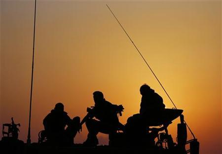 Israeli soldiers sit atop a mobile artillery unit positioned outside the northern Gaza Strip November 20, 2012. REUTERS/Darren Whiteside (ISRAEL - Tags: POLITICS CIVIL UNREST MILITARY)