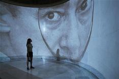 A visitor looks at a projection of a picture of Salvador Dali during a presentation of a new exhibition of his work at Moscow's Pushkin Museum September 2, 2011. REUTERS/Sergei Karpukhin