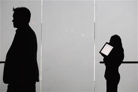 A woman holds an iPad as she makes a phone call at The Cable Show in Boston, Massachusetts May 22, 2012. REUTERS/Jessica Rinaldi/files