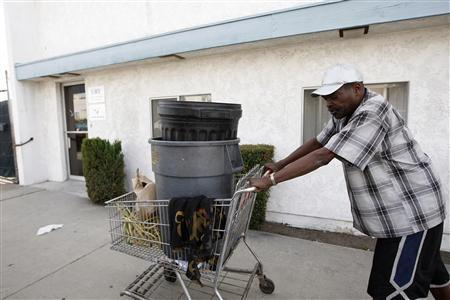 Carnell Weathersby pushes the cart he uses for collecting recyclables after picking up food from the Foothill Unity Center food bank in Monrovia, California, November 14, 2012. The number of people served by Foothill Unity Center has tripled in the last four years. Groups that provide food for pantries say this is one of the toughest years yet in terms of low levels of federal government ''surplus'' commodity donations, which have accounted for a major portion of meat and other proteins in the past. Those shortfalls are putting real pressure on low income families and individuals, who are more squeezed than ever because of still high unemployment, federal and state budget cuts, higher grocery costs from recent drought, rising rents and transport costs. Photo taken November 14, 2012. REUTERS/David McNew