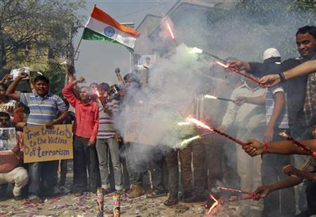 People hold flares and wave India's national flag as they celebrate after India hanged Mohammad Ajmal Kasab, in the western Indian city of Ahmedabad November 21, 2012. India executed Kasab, the lone survivor of a militant squad that killed 166 people in a rampage through the financial capital Mumbai in 2008, hanging him on Wednesday just days before the fourth anniversary of the attack. REUTERS/Amit Dave (INDIA - Tags: CRIME LAW CIVIL UNREST)